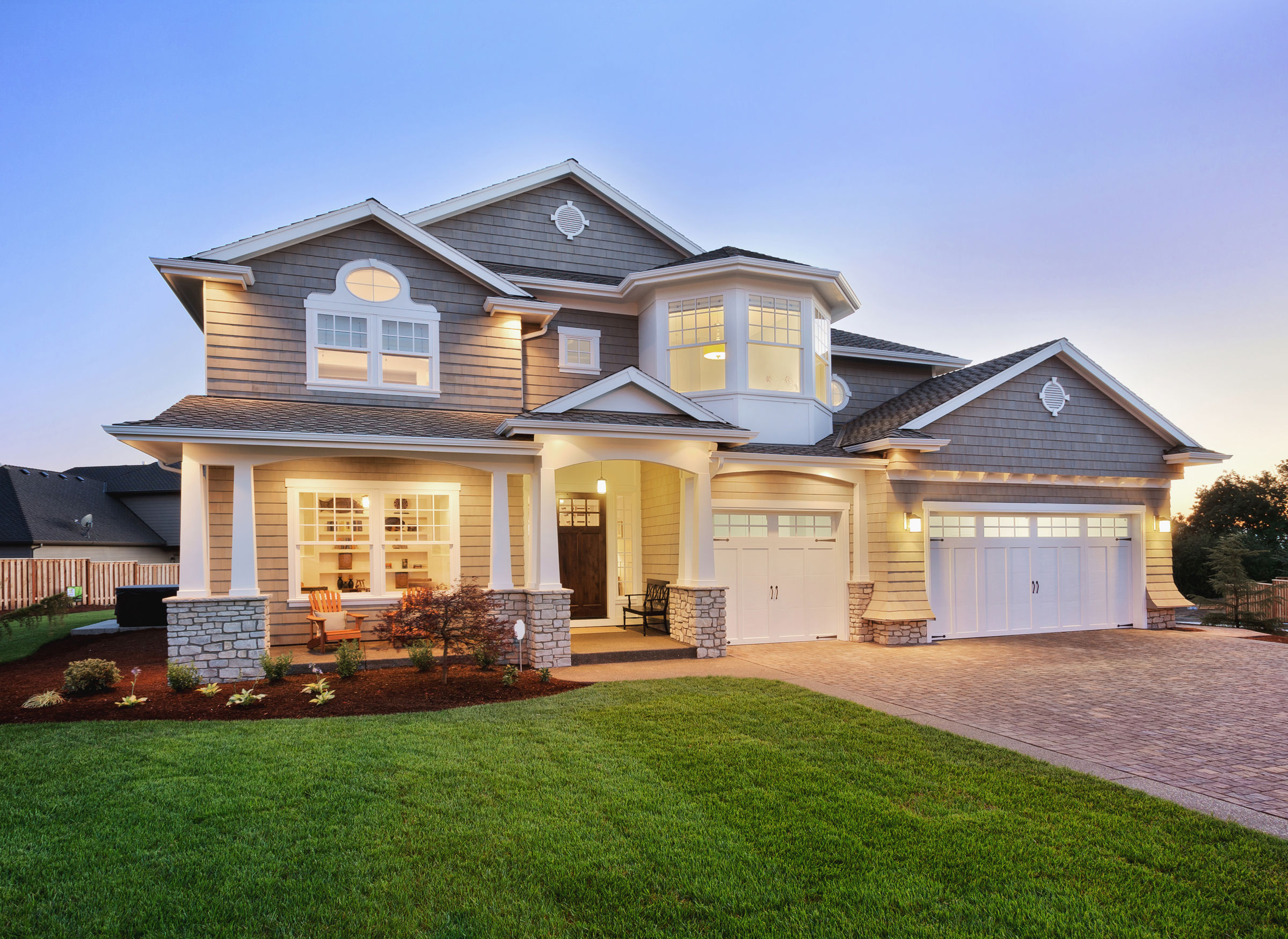 53600574 - home exterior at night/twilight with beautiful green grass three-car garage, and driveway
